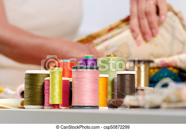 reels of colored threads, seamstress at the bottom - csp50872299