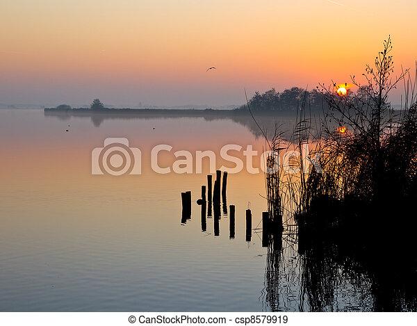 Reflecting sunset over lakeside - csp8579919