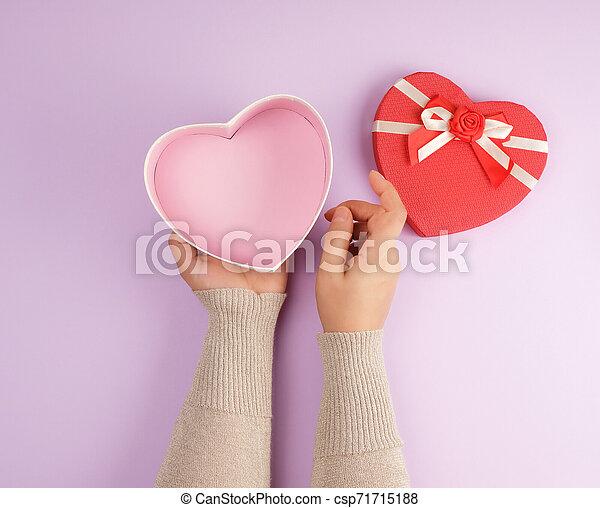 La chica abre una caja de regalos roja en un fondo púrpura - csp71715188
