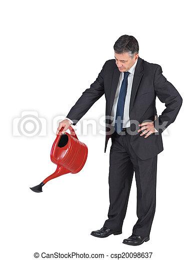 Un empresario maduro regando con lata roja - csp20098637