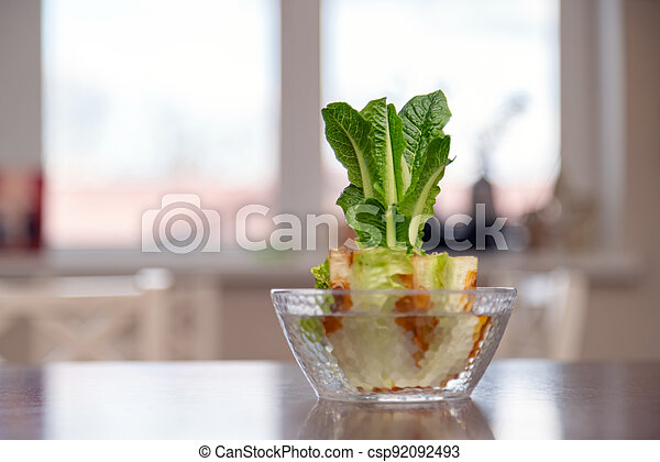 Regrowing chinese cabbage in a glass bowl. Using vegetable scraps to grow organic vegetables at home. - csp92092493