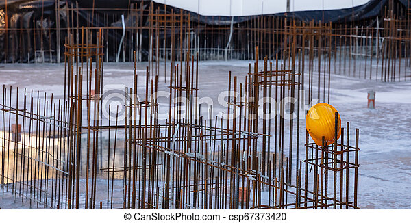Reinforced concrete, under construction. Columns steel bars reinforcement and yellow hardhats - csp67373420