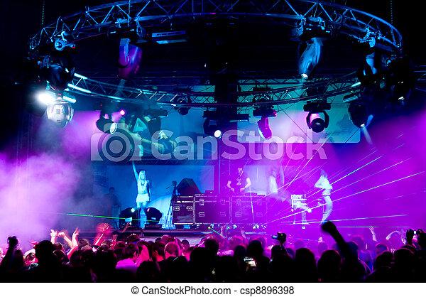 La gente se relaja en el concierto, chicas anónimas en el escenario - csp8896398