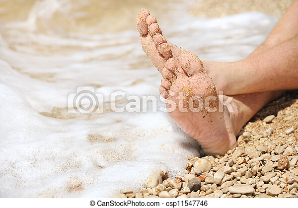 Relaxation on beach, detail of male feet - csp11547746