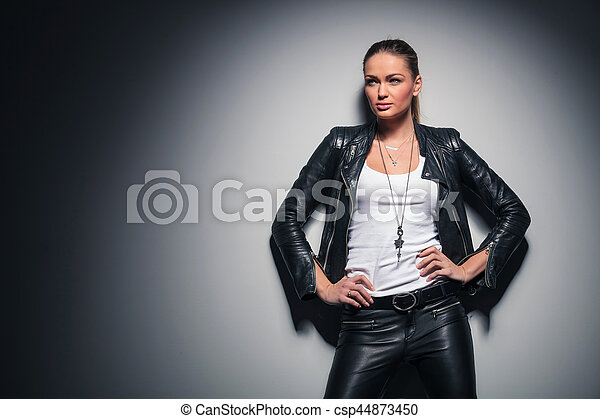 relaxed blonde woman in leather jacket looks away