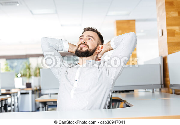 Relaxed businessman sitting in office with hands behind head - csp36947041