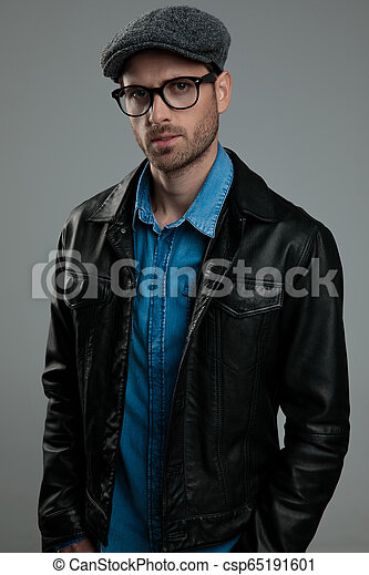 Portrait of relaxed fashion man wearing leather jacket and flat cap ... 3eff88305c2