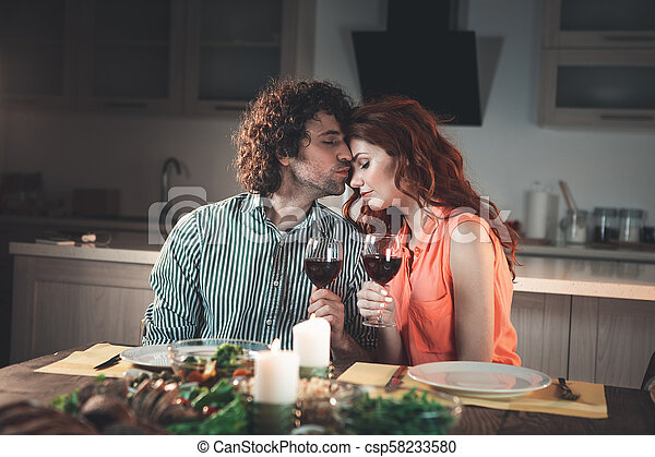 Relaxed loving couple having candlelight dinner - csp58233580