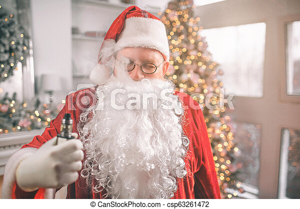 Relaxed man in Santa Claus costume stands and holds vape in hand. Smoke comes out of his mouth. He is relaxed. - csp63261472