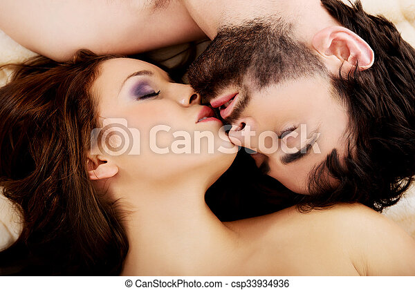 Relaxed Young Couple Kissing In Bed.   Csp33934936
