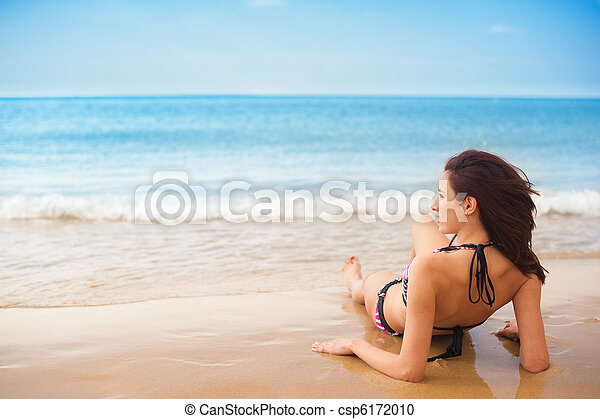 relaxing at the beach female model sitting back relaxing on sand