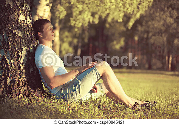 Relaxing man sitting under a tree with eyes closed meditating and enjoying the warm evening sunset in profile - csp40045421