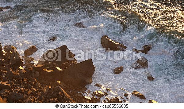 Relaxing ocean waves crashing into rocky shore. - csp85556005