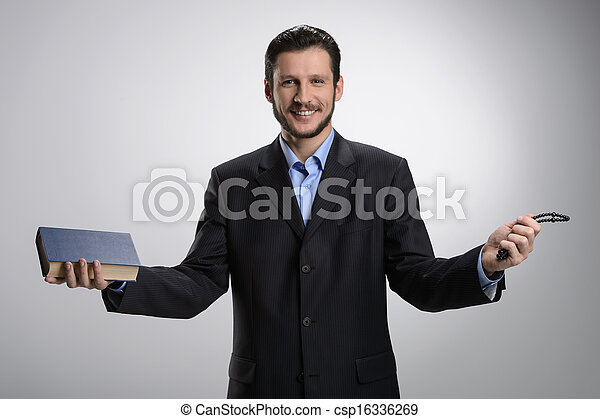 Religious businessman. Cheerful bearded man in formalwear holding the Holy Bible and rosary beads in his hands while isolated on grey - csp16336269