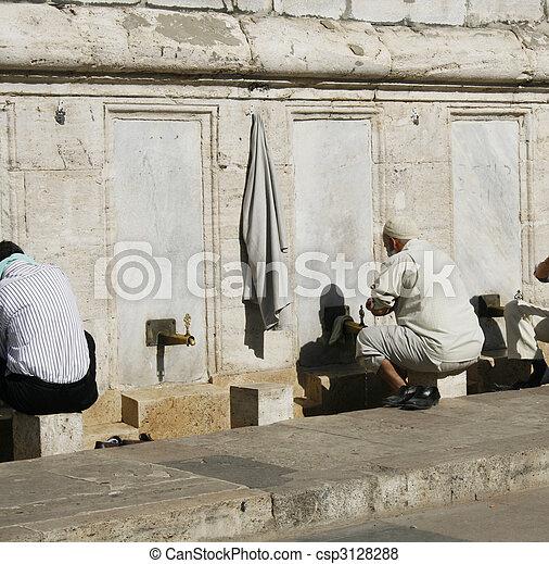 religious men washing feet near mosque - csp3128288
