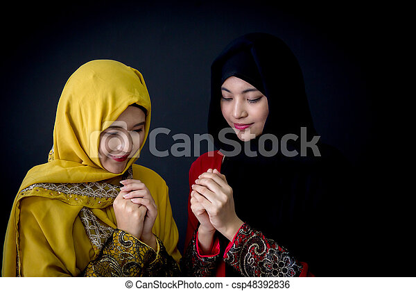 religious young muslim two women praying over black background