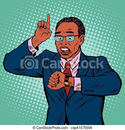 Un hombre de negocios afroamericano mirando reloj de pulsera - csp41075594
