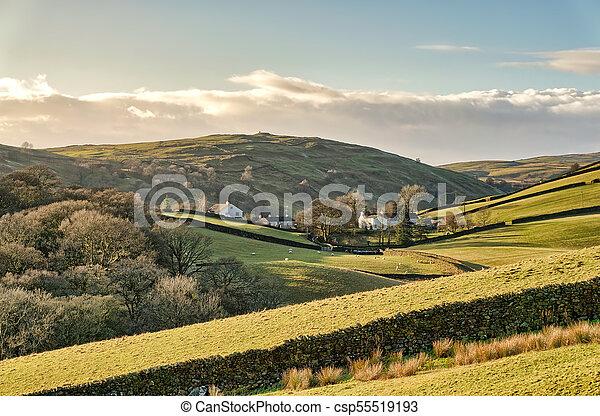 Remote farm buildings hidden in a valley. - csp55519193