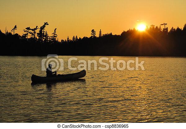 Pescando en una canoa puesta de sol en un remoto lago salvaje - csp8836965