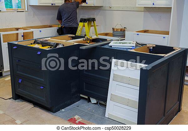 Repair man In Overalls Repairing Cabinet Hinge In Kitchen