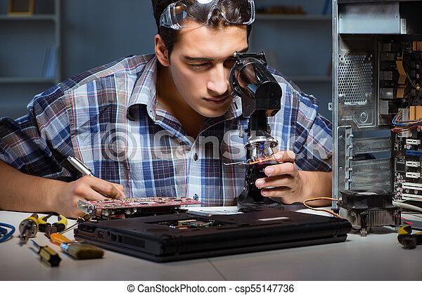 Repairman trying to repair laptop with miscroscope - csp55147736