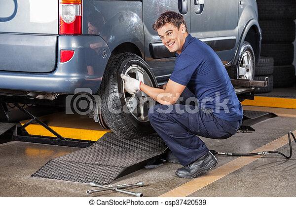 Fröhlicher Mechaniker, der Autoreifen repariert - csp37420539