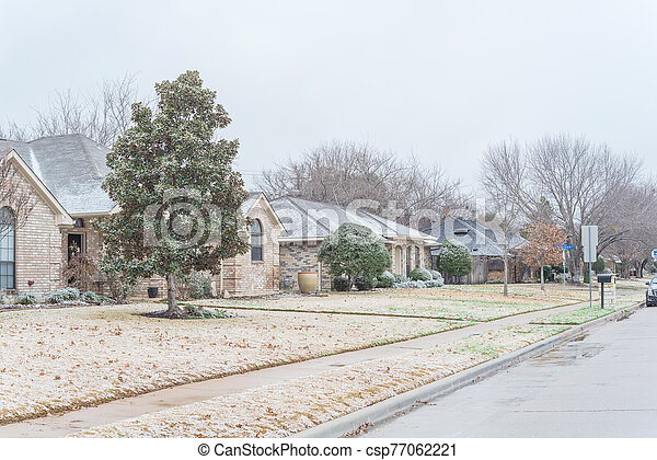 Residential street with bungalow houses under winter snow cover near Dallas - csp77062221