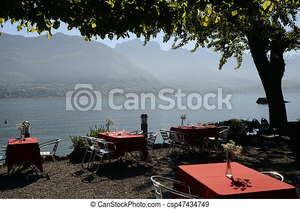 Restaurant terrace with red tables and annecy lake landscape, France