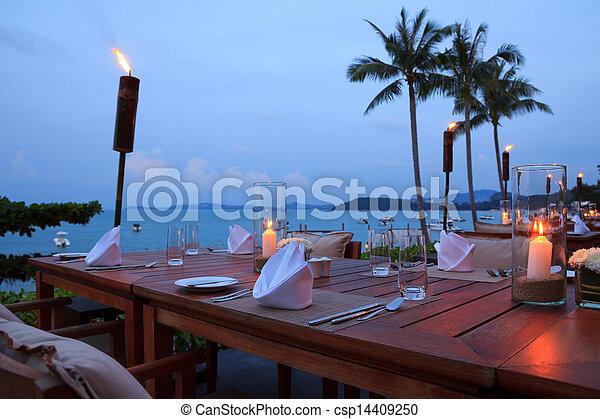 Mesas de restaurantes al aire libre, cenando en la playa en Sunset - csp14409250