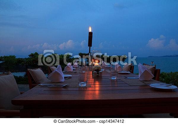Mesa de restaurante al aire libre, cenando en la playa por la noche - csp14347412