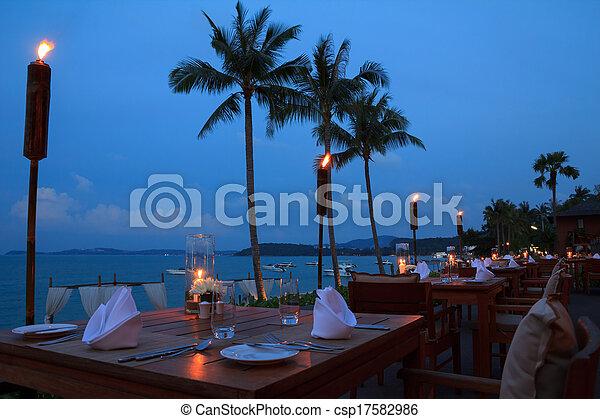 Mesas de restaurantes al aire libre, cenando en la playa por la noche - csp17582986