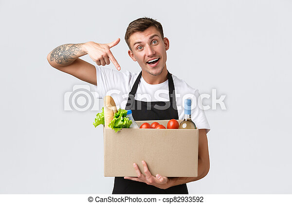 Retail, grocery shopping and delivery concept. Handsome courier in black apron handing over box with groceries, salesman prepared package, pointing at box with food groceries, white background - csp82933592