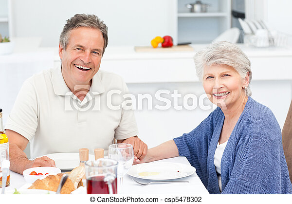 Retired couple eating  in the kitchen - csp5478302