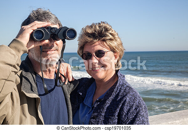 Retired couple on beach vacation with Binoculars - csp19701035