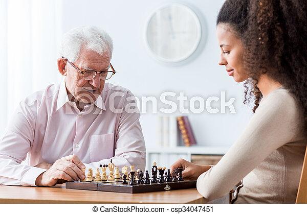 Retired man playing chess - csp34047451