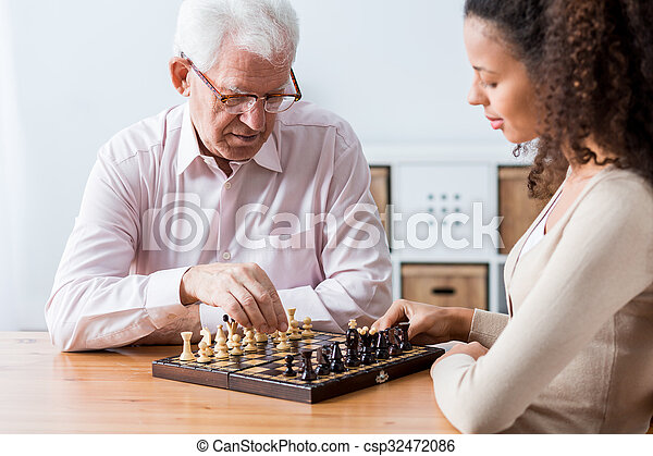 Retiree and caregiver playing chess - csp32472086