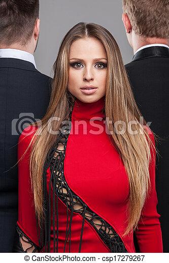 Una sesión de fotos de chicas rubias sexys con vestido rojo y dos tipos con traje negro. Vista trasera de los hombres y primera vista de la mujer - csp17279267
