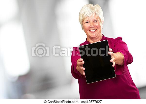 Retrato de una anciana sosteniendo un portátil - csp12577627