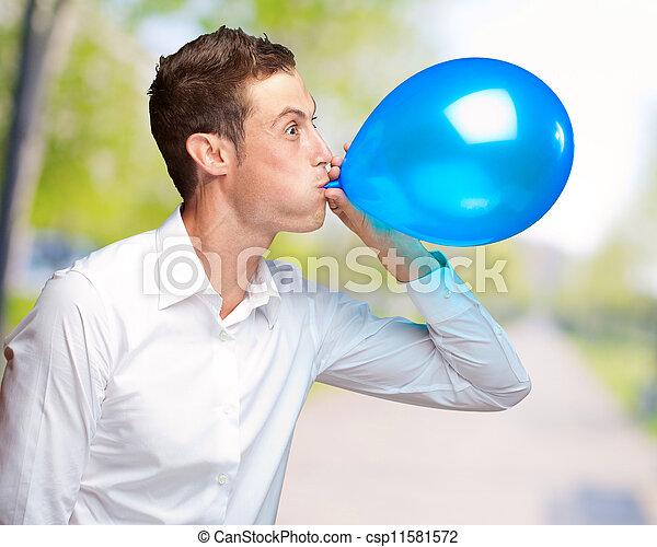 Retrato de un joven soplando un globo - csp11581572