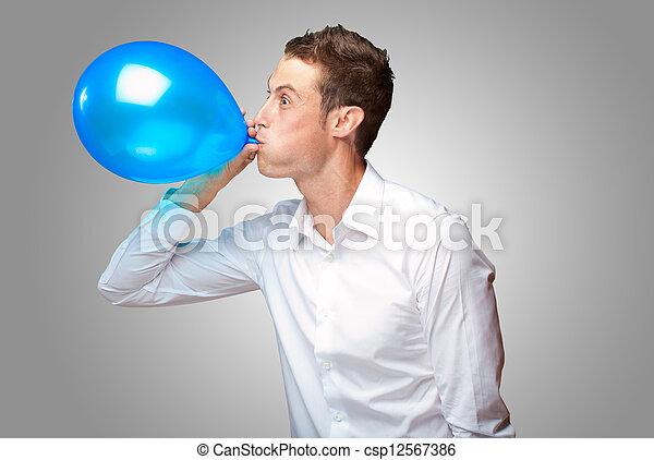 Retrato de joven soplando un globo - csp12567386