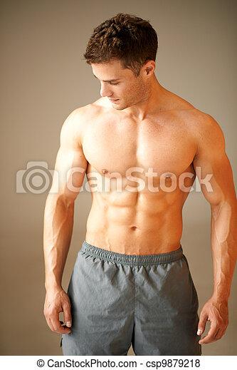 Retrato de musculoso deportista parado en marrón - csp9879218