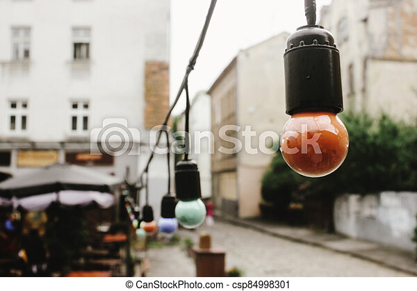 retro beautiful lamp lights on garland at cafe terrace in the street in europe city holiday, space for text - csp84998301