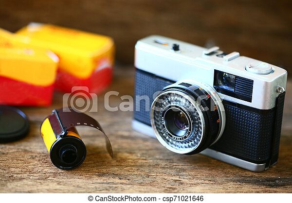 Retro camera with film for photography. Photographer love to take photo with old camera and film with feeling classic. The film camera not popular in present because digital camera instead. - csp71021646