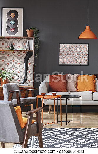 Retro living room interior with armchairs, sofa decorated with orange  pillows, coffee table, poster, cupboard and patterned carpet