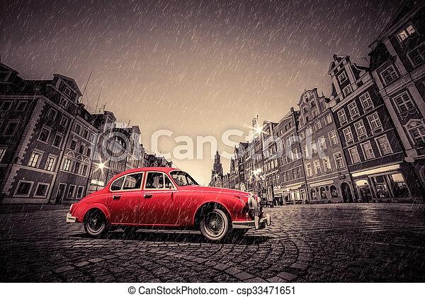 Retro red car on cobblestone historic old town in rain. Wroclaw, Poland. - csp33471651