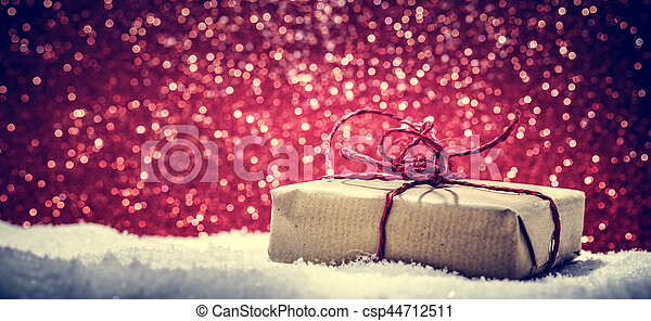 retro rustic christmas gift present in snow on glitter background handmade eco paper wrap