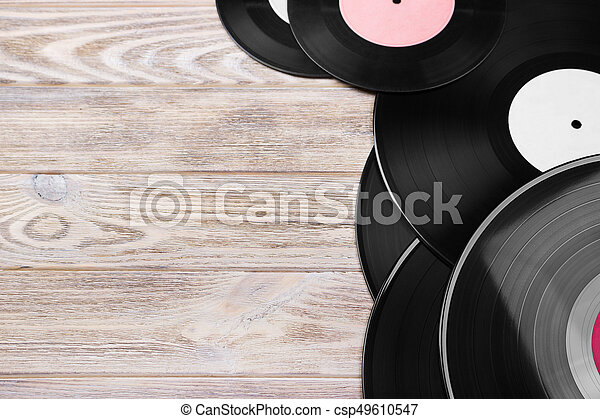 Retro vinyl records on the bright wooden background, selective focus. Top view. Copy space - csp49610547