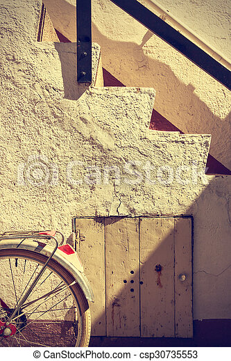 Retro wheel bicycle detail and old stairs. Vintage style. - csp30735553
