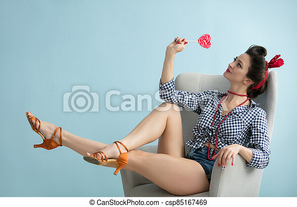 Retro woman in a chair with a lollipop. - csp85167469