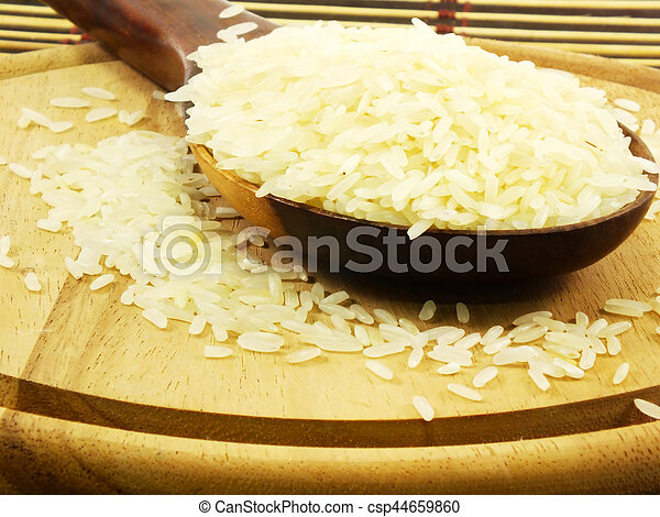 rice on wooden ladle close up - csp44659860
